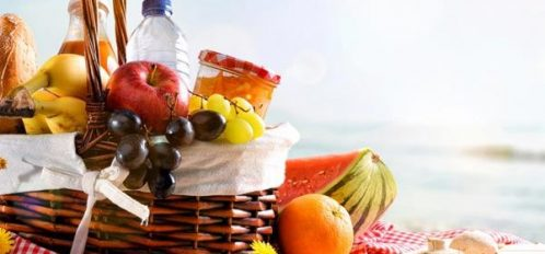 Picnic Basket with fruits and other foods by the sea